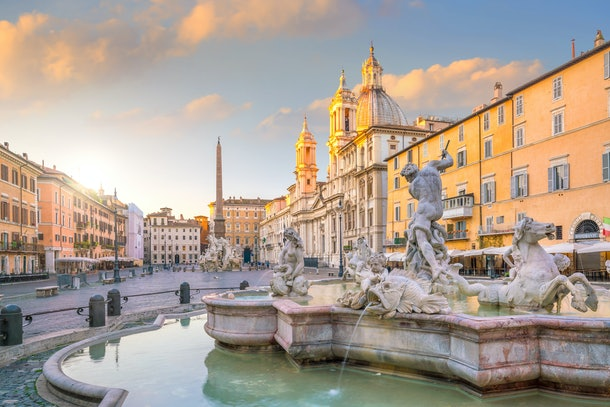 A landscape photo of a fountain, monument, and square in Rome at sunrise.