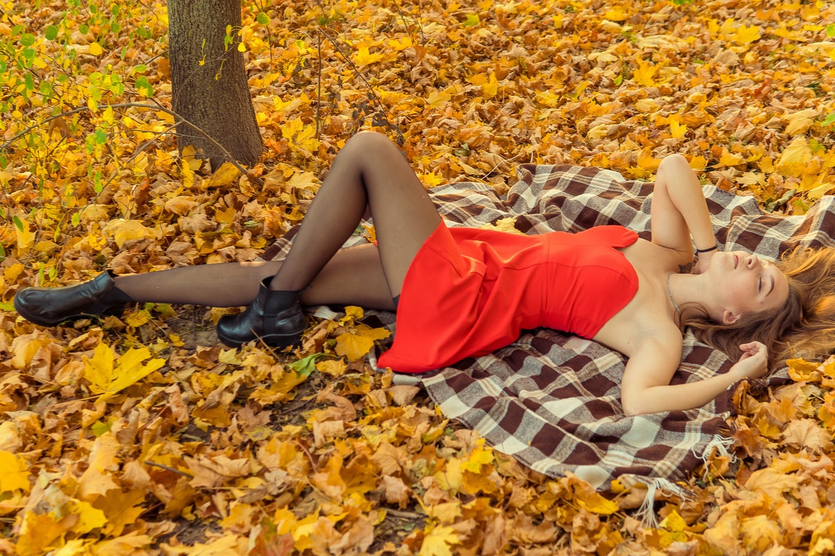A woman is posing in front of a camera in an autumn park. autumn photo shoot. Autumn in the park.