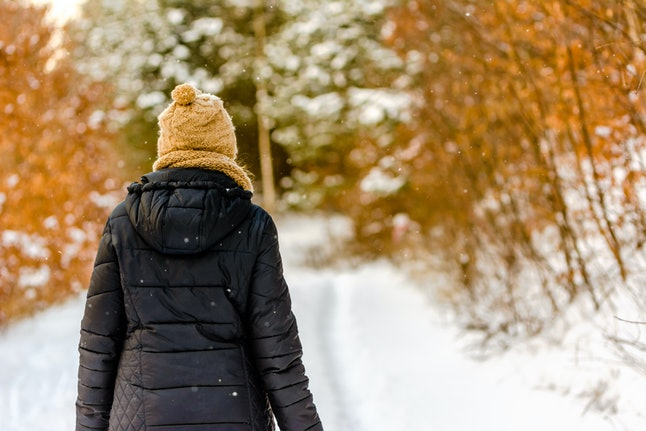 Woman in winter clothes. Girl walking in snow in park, outdoors