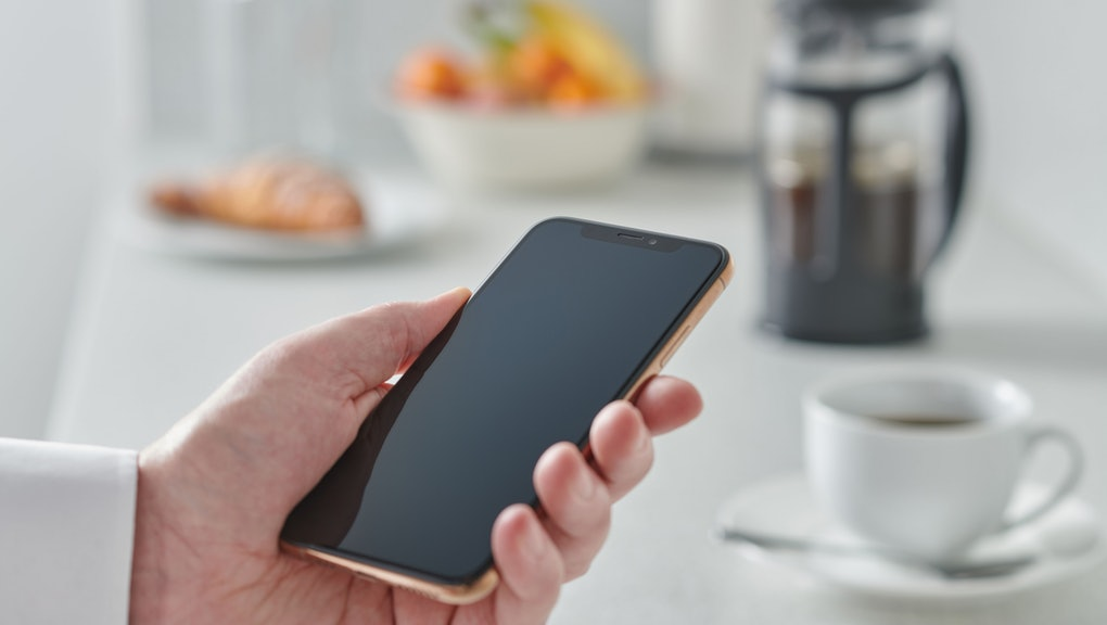 Close Up Detail Of A Man Holding A Smartphone Over A Kitchen Counter