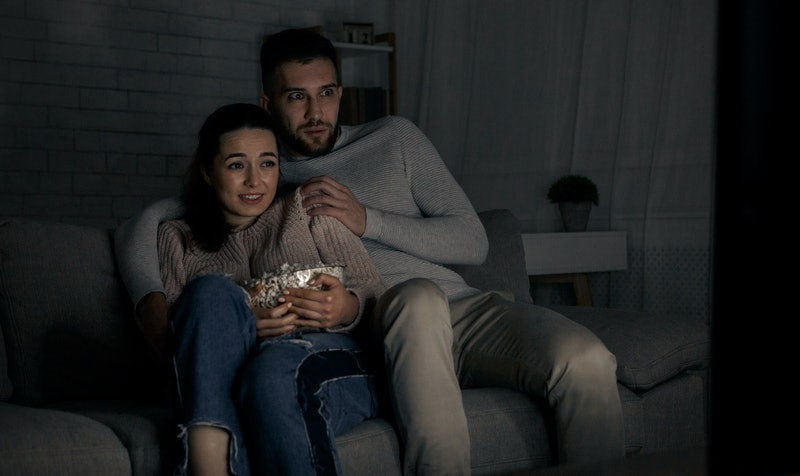 Scared couple watching horror film late at night at home