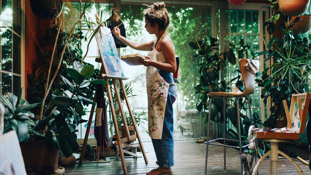 Indoor shot of professional female artist painting on canvas in studio with plants.
