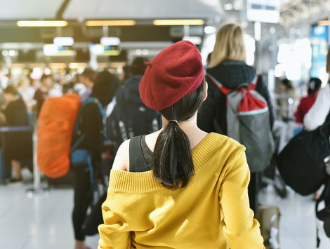 Airline check-in counter queue at international airport with blurred of crowded passenger background, Asian woman traveler waiting hour long for boarding security check line.