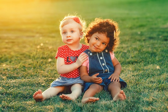 Group portrait of two cute adorable girls toddlers children sitting together. White Caucasian and la...