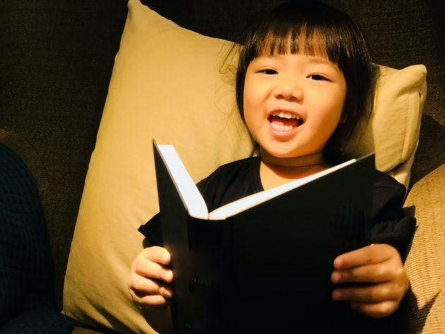 A Happy Cute little Asian girl (4 years old) reading a book and smiling while lying alone on a sofa in the room.