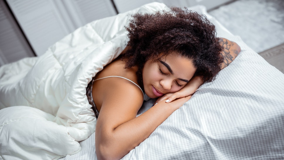 Dark-skinned woman resting. Curly short-haired lady putting head down on connected hands during deep sleep