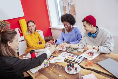 Students painting. Four creative art students painting on white sheets of paper while having drawing...