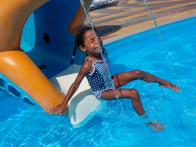 Mixed ethnicity little smiling girl coming down on the chute into the water. On the slide in aqua park after going down in children's swimming pool