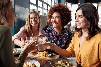 Four Young Female Friends Meeting For Drinks And Food Making A Toast In Restaurant