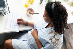 Focused on writing. Pregnant woman making notes about her body changing while having breakfast.