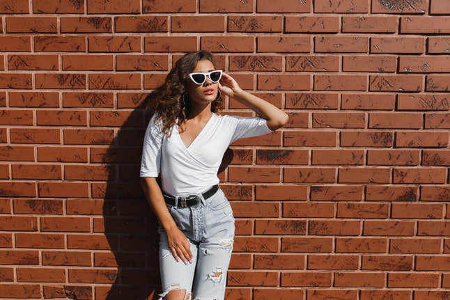Attarctive elegant young woman hipster in a white sunglasses in a summer denim pants and white t-shirt with curly brunette girl posing near the red brick wall outdoors.