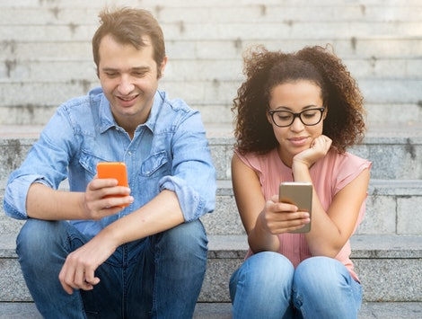 Two friends using their mobile phones seated together