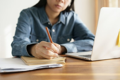 Asian women take notes with a pencil in the office, business woman working