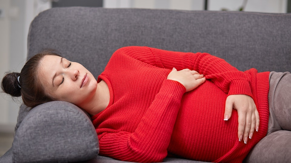 Photo of sleepy tired pregnant woman takes nap, keeps hands on belly, wears red warm sweater, enjoys good rest on sofa at home, calm atmosphere. People, sleeping, pregnancy, motherhood concept