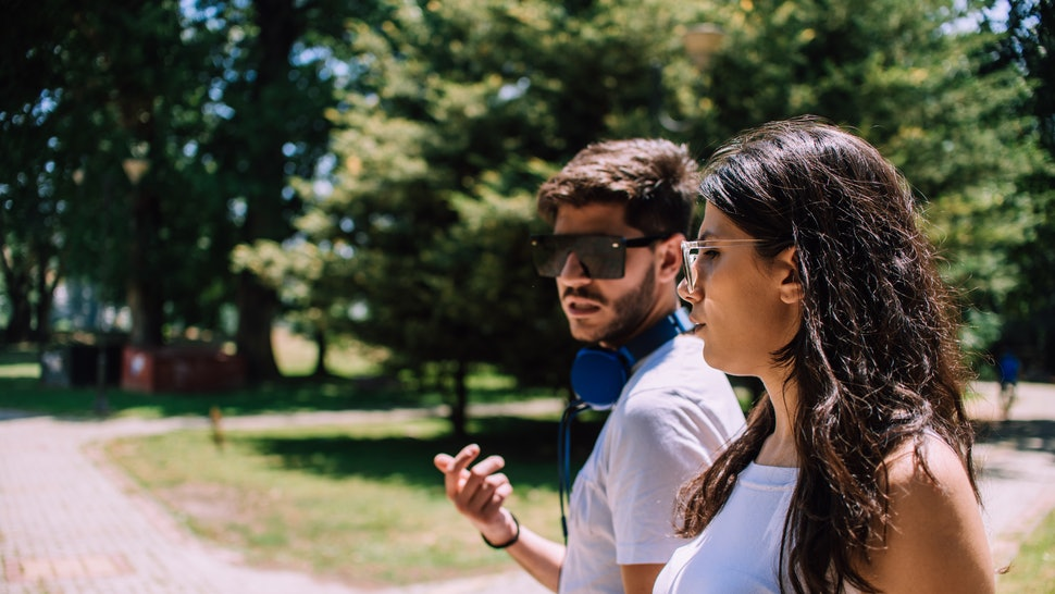Couple talking seriously outdoors in a park with a green background