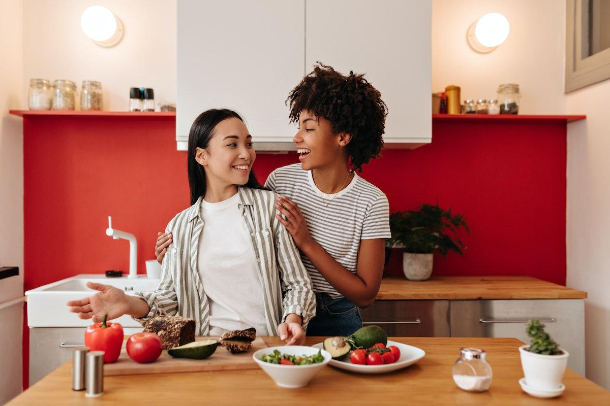 Girl hugs friend by shoulders in kitchen. Dark-haired women make salad