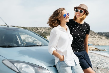 Two beautiful young women travel by car.
