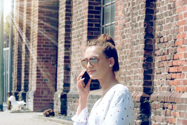 A young woman is on the phone with a smartphone