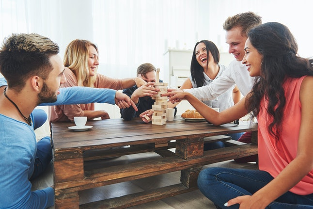 Group of creative friends sitting at wooden table. People having fun while playing board game.