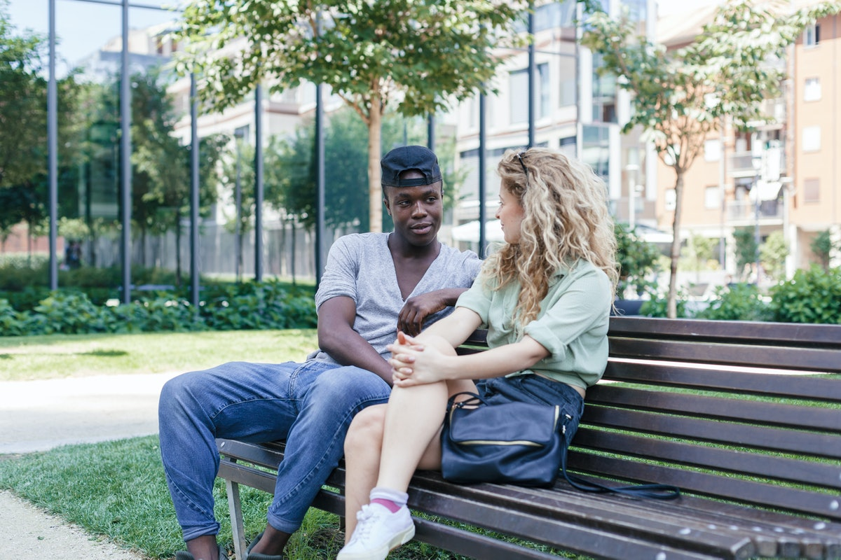 Engaged couple talking on bench in a park during summer