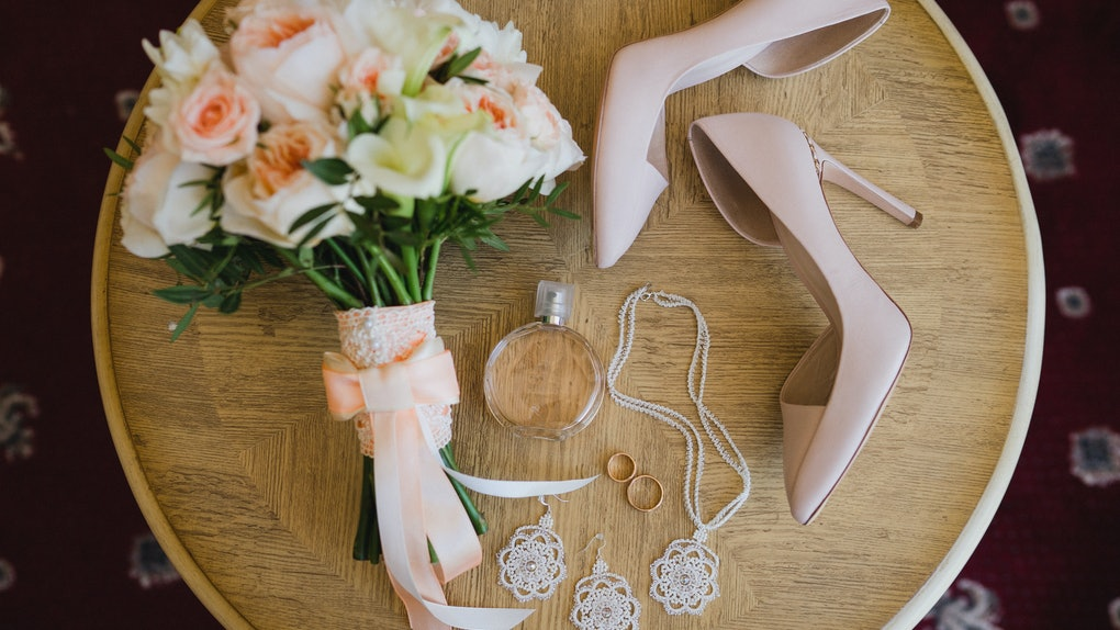 Botanic bridal chic. Bouquet with silk ribbons, female classic shoes, perfume bottle, necklace, earrings, wedding rings and shoes on vintage table.