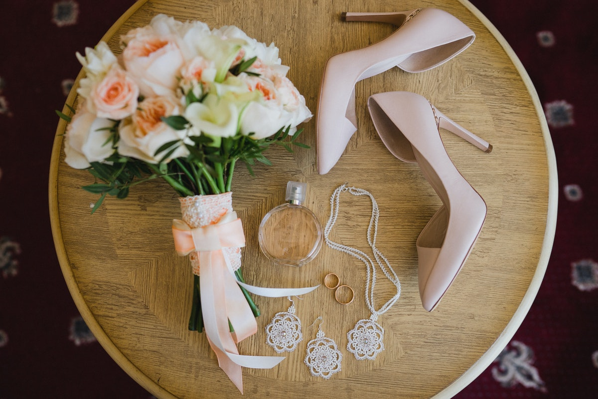 Botanic bridal chic. Bouquet with silk ribbons, female classic shoes, perfume bottle, necklace, earr...