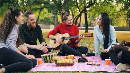 Charming young woman is playing the guitar sitting on blanket with friends on picnic, girls and guys are clapping hands and listening to music. Fun and nature concept.