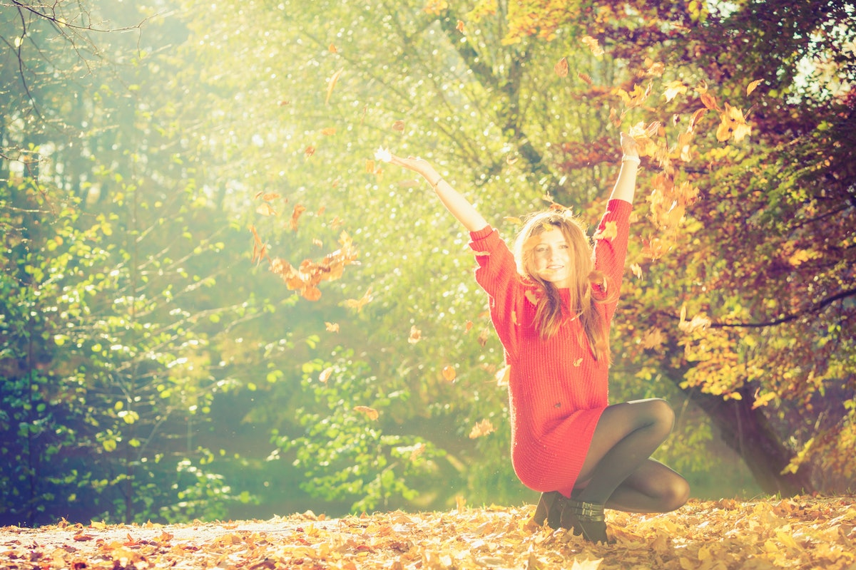 Autumn time. Fun and carefree. Cheerful lovely young woman playing with leaves. Girl relax in autumn...
