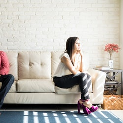 Husband and wife sitting on the couch and not talking after an argument at home