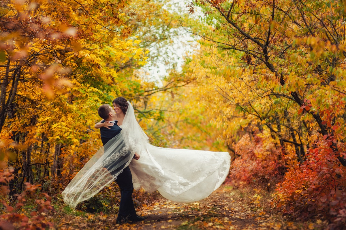 Happy young newly married wedding couple on walk in golden yellow fall autumn park around trees. Gro...