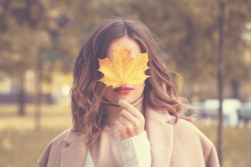 Beautiful Autumn Woman with Autumn Leaves on Fall Nature Background