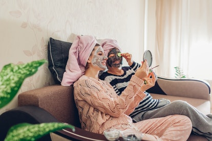 Mother and her adult daughter applying facial masks and cucumbers on eyes. Women chilling and having...