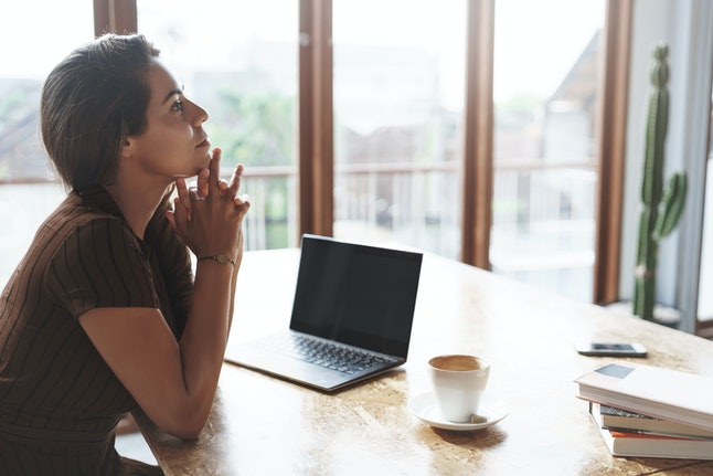 Attractive lucky successful businesswoman listening employees reports sit satisfied pleased near window, laptop opened drink coffee hold hands above chin thoughtful, thinking make decision