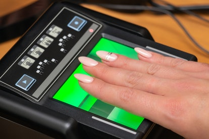 The process of scanning fingerprints during the check at border crossing. Female hand puts fingers t...