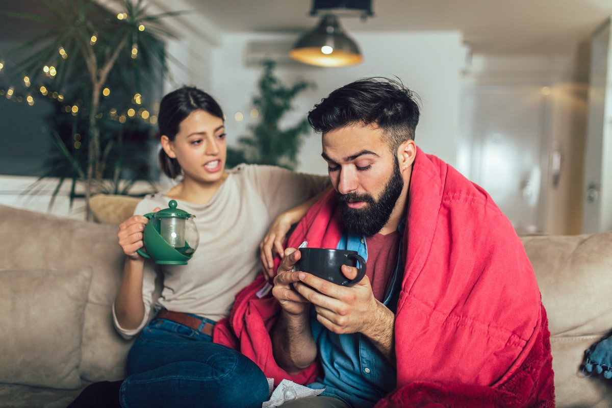 Woman taking care of her sick boyfriend lying on the sofa