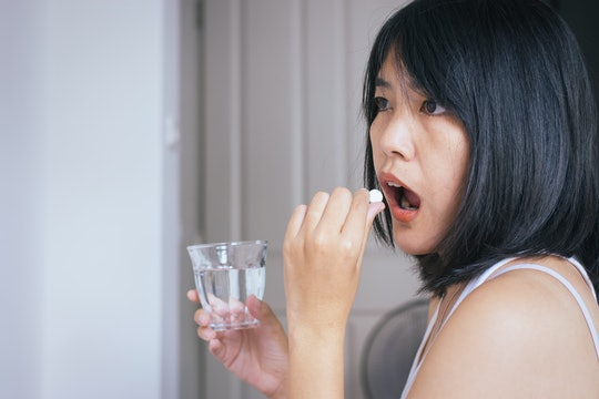 Woman sick with pill putting in her mouth,female taking medicines and a glass of water,Concept for health