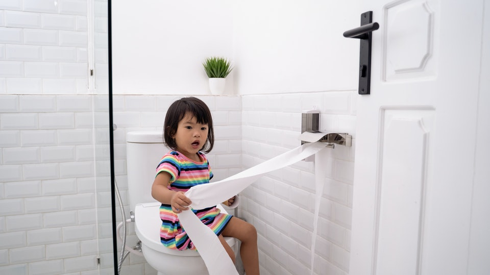 toddler pulling out toilet paper while playing around in the bathroom