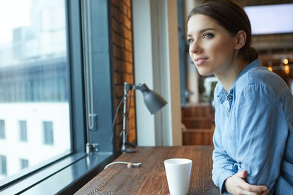 Young attractive girl  sitting alone near big window in coffee shop during free time and working