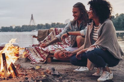 No cares. Group of young people in casual wear roasting marshmallows over a campfire while resting n...