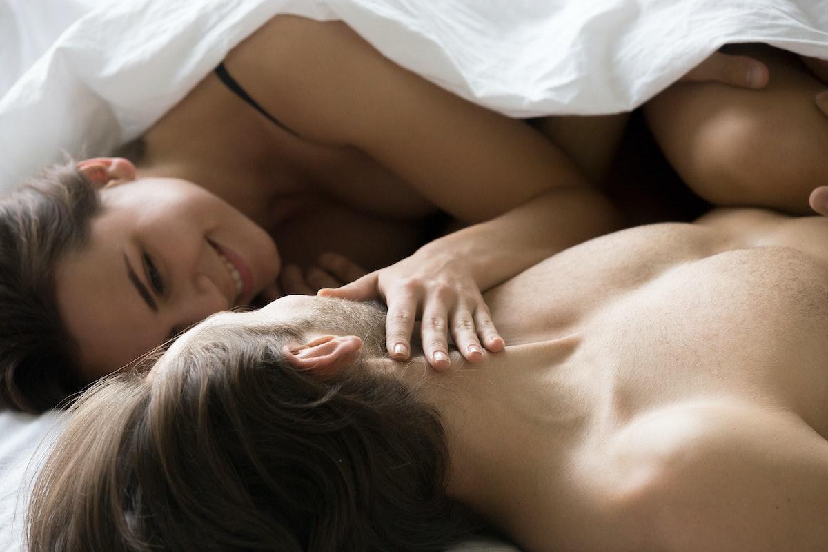 Smiling girlfriend look in boyfriend eyes smiling, sensual couple enjoying romantic moment in bed, w...