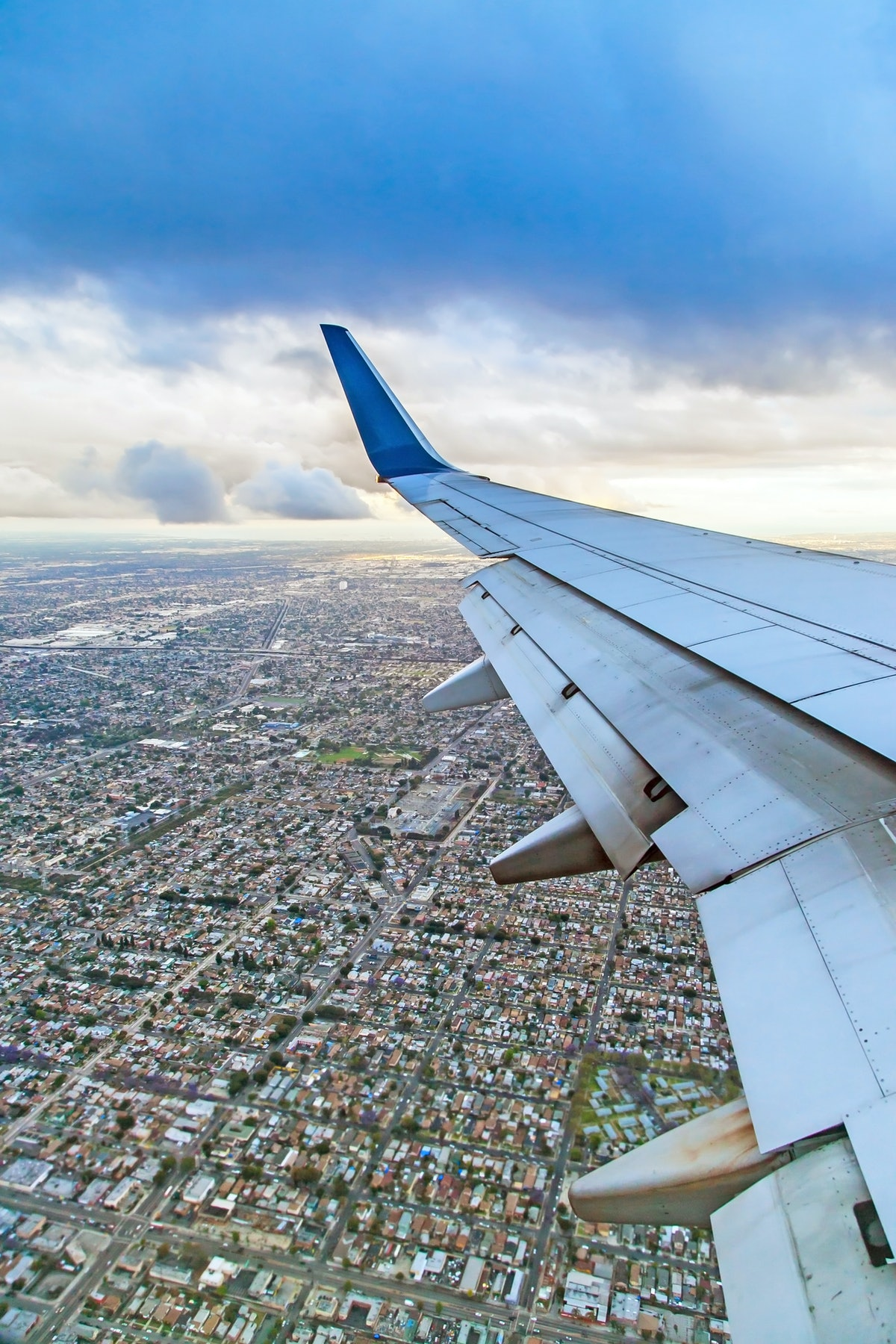 Landing airplane and top view of Los Angeles city  from window flying over clouds in blue sky, journey concept