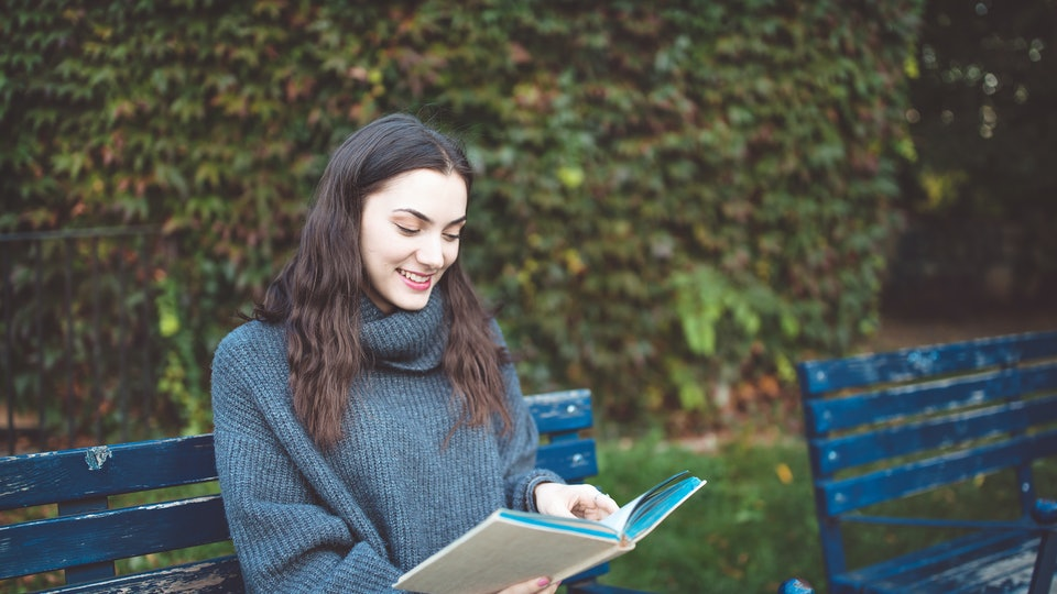 Young woman in a sweater reading a book, sitting on the bench in the park. Autumn time.