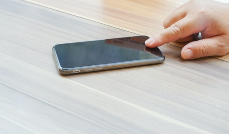 A business man hand touch a Smart Phone for unlock the phone
