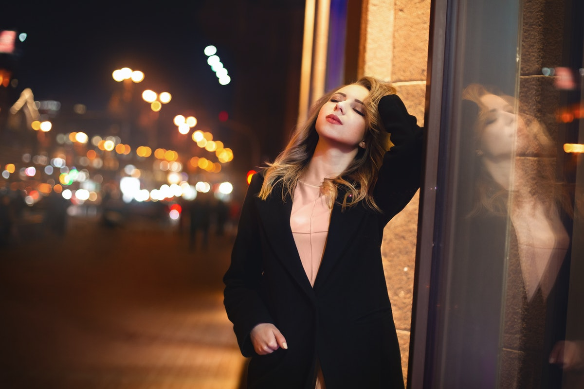 portrait of Beautiful young woman in black on a background of a night city