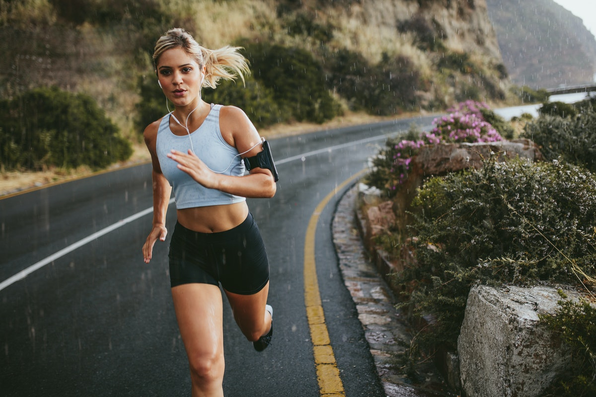 Female athlete running outdoors on highway. Beautiful young woman training running on a rainy day.