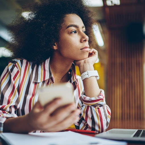 Pondering african american young woman thinking on creative ideas for publication in blog on smartphone device sitting in coffee shop.Thoughtful dark skinned hipster girl looking out of window