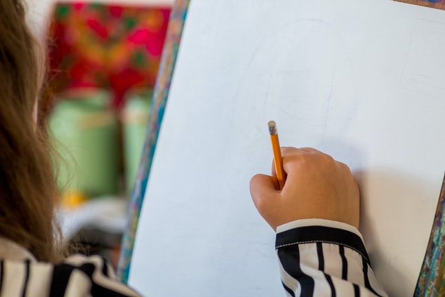 person draws at the easel