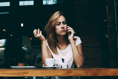 Young woman is having unpleasant conversation on mobile phone with her husband, because of jealousy. Concerned female have in bad mood tis talking on cell telephone while sitting alone in coffee shop