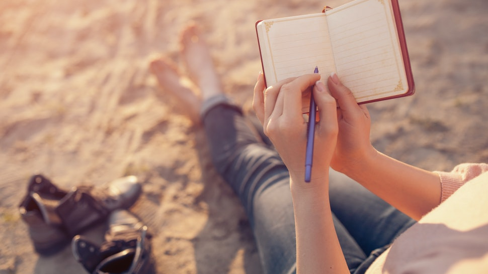 woman writes in diary and sitting on sand; female makes notes and sitting on the beach;