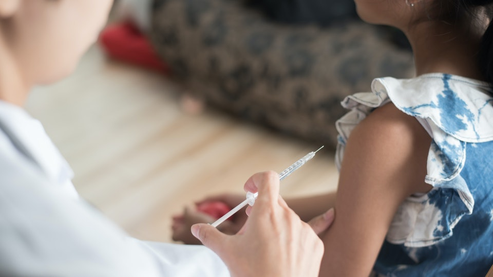Close up of doctor vaccinating young girl, Vaccination concept.